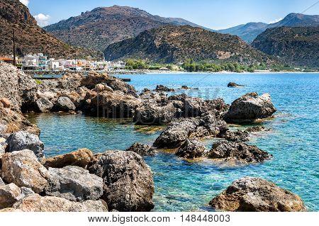 Rocky coastline  with Paleochora ton on a background at Crete island, Greece
