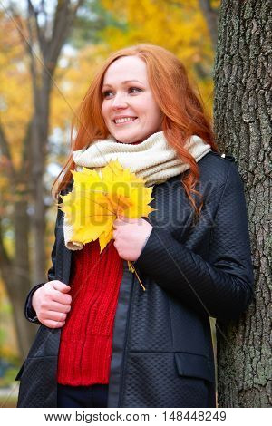 girl portrait with yellow leaf in hand in autumn forest, stand near big tree