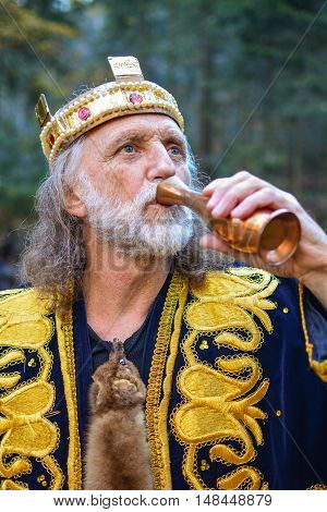 Portrait of old king drinking from the goblet outdoors in the middle of autumn forest