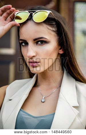 Attractive young girl with long hair wearing suit posing on a background of shops showcases