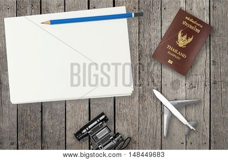 Air Travel objects on wood with blank notebook page