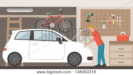 Home garage with car bike and tools hanging on the wall a man is repairing the car