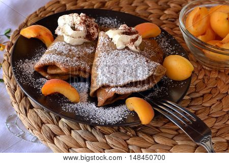 Homemade pancakes with jam, apricots, whipped cream and icing sugar.