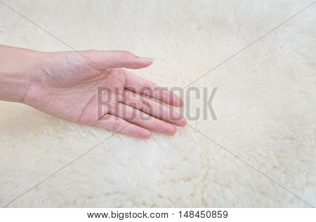 Closeup woman hand on white fabric carpet made from wool textured background