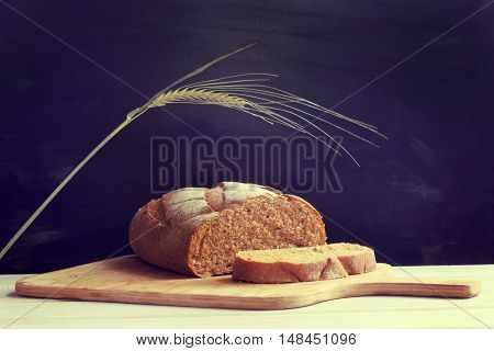 sliced traditional bread lays on a wooden board on a dark background / healthy product for a healthy lifestyle