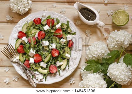 Salad with avocado kiwi strawberry feta and arugula