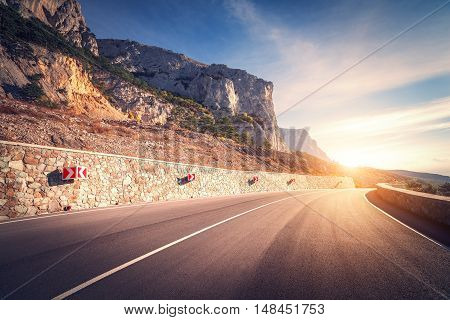 Asphalt road. Colorful landscape with beautiful mountain road with a perfect asphalt and road signs. Sunrise in summer. Vintage toning. Travel background. Highway at mountains. Speed. Retro style