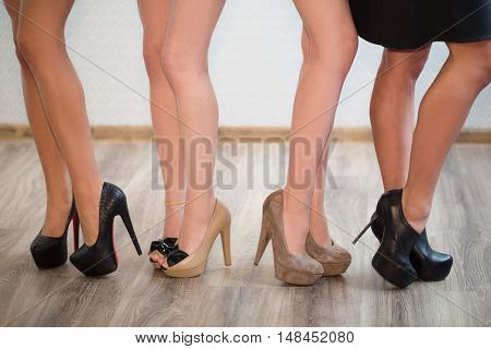 Four pair long female legs with high-heeled shoes
