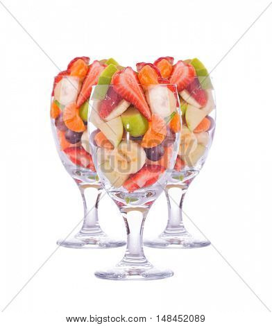 Three colorful, healthy fruit salads in a large glasses, isolated on white