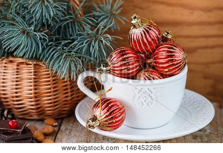 Christmas composition. Red little balls in a white Cup spruce branches chocolate cranberries and almonds on the table