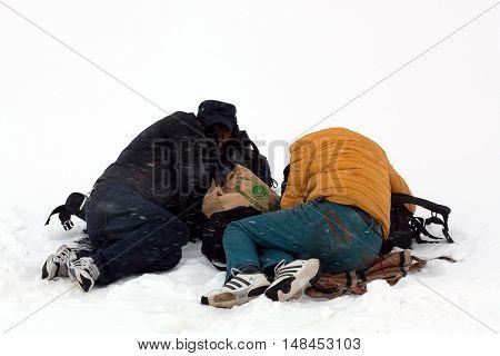 NGARI, TIBET - MAY 6, 2013: Two Tibetan pilgrims sleeping over snow during snowstorm on the trail around sacred mount Kailash in Ngari Prefecture, Tibet Autonomus Region of China.