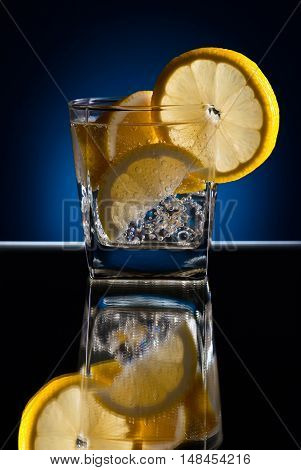 Gin with tonic; ice and lemon on a reflective background