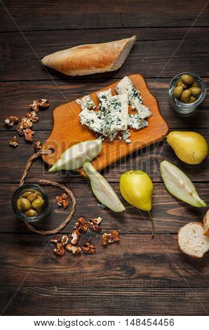 Blue cheese with walnuts, olive and pears on rustic table.