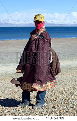 NGARI, TIBET - MAY 7, 2013: Young Tibetan pilgrim in national clothes on the trail around holy Manasarovar lake in Tibet Autonomus Region of China