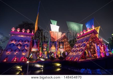 KOLKATA INDIA - OCTOBER 21 2015 : Beautiful exterior of decorated Durga Puja pandal at night Howrah West Bengal India. Shot under colored lights. Durga Puja is biggest religious festival of Hinduism.