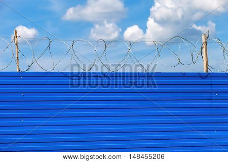 Barbed wire on the fence against a blue sky background. Restricted area