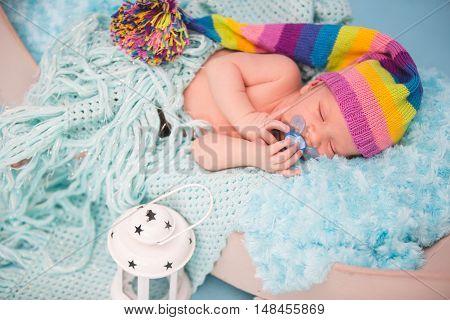 Studio portrait of newborn baby boy sleeping in bed.