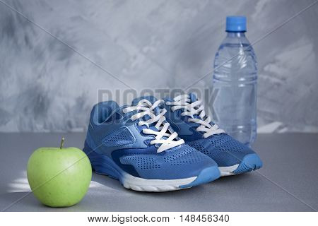 Sport shoes apple bottle of water on gray concrete background. Concept healthy lifestyle sport and diet. Sport equipment. Focus is only on the sneakers.