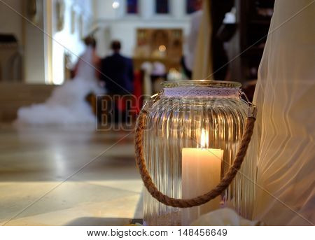 A wedding candle with a married couple during the wedding ceremony