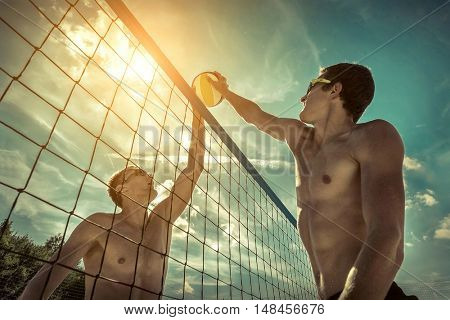 Beach Volleyball players in sunglasses under sunlight. Dynamic sport action outdoor.