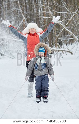 Mother and little son stand under snow powder in winter park.
