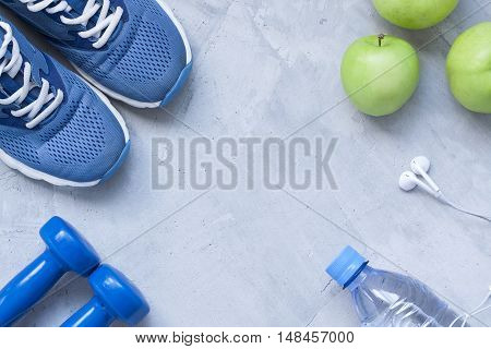 Flat lay sport shoes dumbbells earphones apples bottle of water on gray concrete background. Concept healthy lifestyle sport and diet. Selective focus. Flat lay shot of Sport equipment.