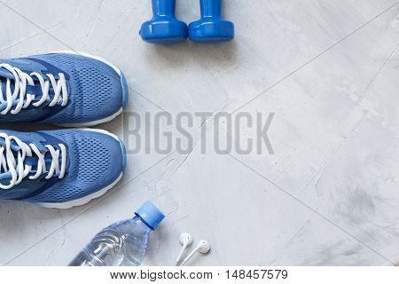 Flat lay sport shoes bottle of water dumbbells and earphones on gray concrete background. Concept healthy lifestyle sport and diet. Focus is only on the sneakers. Sport equipment.