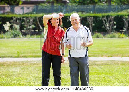 Tired Senior Couple Standing In Park Holding Bottle Of Water