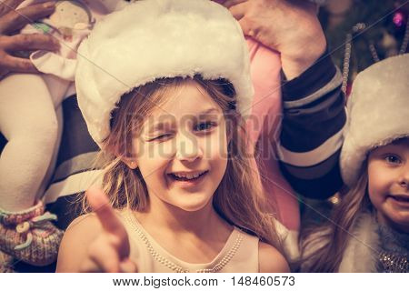 Winking child looking at camera with approval gesture during Christmas holidays