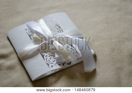 White openwork postcard with a satin ribbon on a beige background of textile