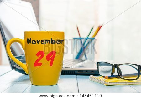 November 29th. Day 29 of month, hot drink cup with calendar on human-resources manager workplace background. Autumn time. Empty space for text.