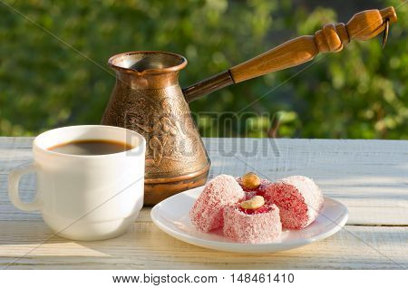 Turkish delight coffee mug and the Cezve in the sunlight on a background of green pleasant evening