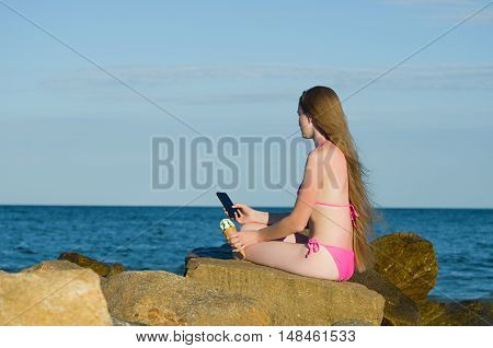 Girl thoughtfully looking into the phone in a bathing suit on the beach