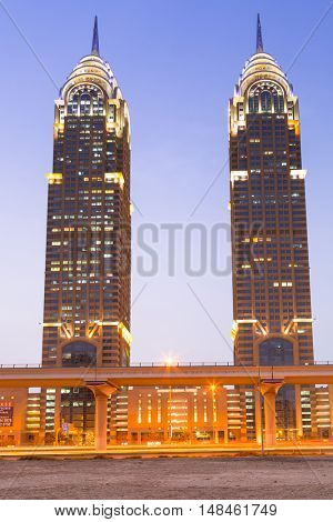 DUBAI, UAE - 3 APRIL 2014: Business Central Towers in Dubai Media City at night. The Al Kazim Towers is a complex of two 53-floor towers, resemble to the New York City's Chrysler Building.