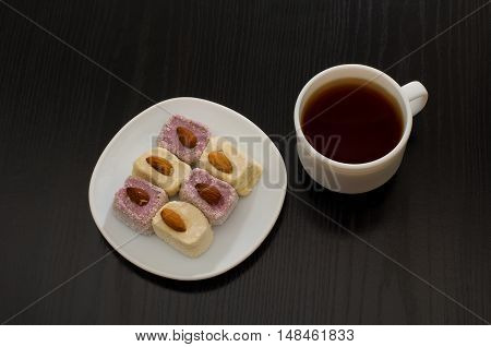 Top view of Turkish delight with almonds and cup of coffee black table