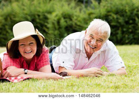 Smiling Senior Couple Lying On Grass In Park