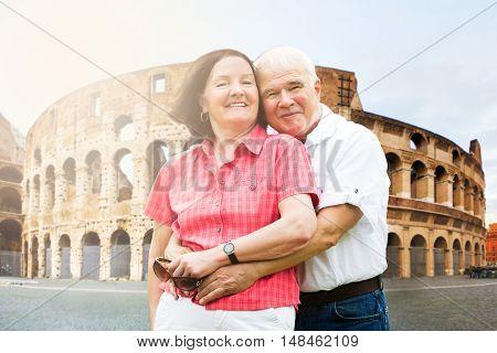 Portrait Of A Happy Senior Couple In Front Of Coliseum
