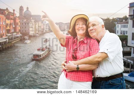 Smiling Senior Couple Pointing Finger In Front Of Grand Canal In Venice