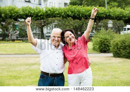 Portrait Of Elder Senior Couple Raising Their Arms In Park