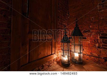wooden door in brick room with candles. Winter Is Coming.
