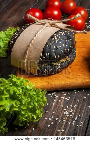 Delicious black burgers in craft paper on cutting board on dark wood table.