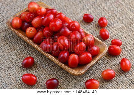 Cranberries, cornelian cherries in a wooden bowl on  burlap