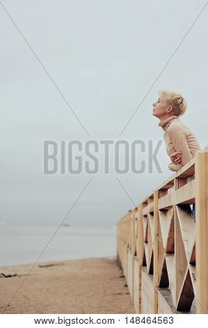 Young Caucasian Woman Standing In A Pavilion On The Sea Shore Leaning Over Railing