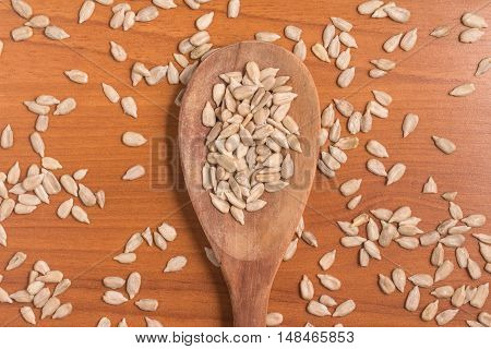 Sunflower Seeds into a spoon over a wooden table