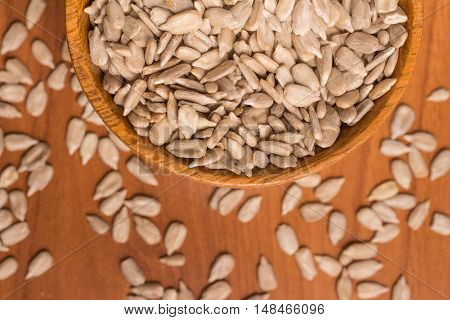 Sunflower Seeds into a bowl over a wooden table