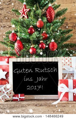 Colorful Christmas With Tree With Balls And Snowflakes. Gifts Or Presents In The Front Of Wooden Background. Chalkboard With German Text Guten Rutsch Ins Jahr 2017 Means New Year 2017