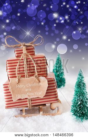 Vertical Image Of Sleigh Or Sled With Christmas Gifts Or Presents. Snowy Scenery With Snow And Trees. Blue Sparkling Background With Bokeh. Label With English Text Merry Christmas And Happy New Year