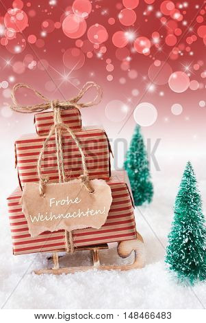 Vertical Image Of Sleigh Or Sled With Christmas Gifts Or Presents. Snowy Scenery With Snow And Trees. Red Sparkling Background With Bokeh. Label With German Text Frohe Weihnachten Mean Merry Christmas