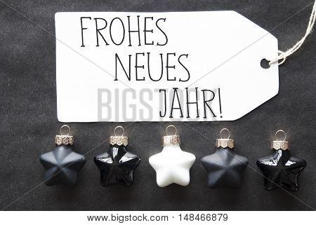 Label With German Text Frohes Neues Means Happy New Year. Black And White Christmas Tree Balls On Black Paper Background. Christmas Decoration Or Texture. Flat Lay View