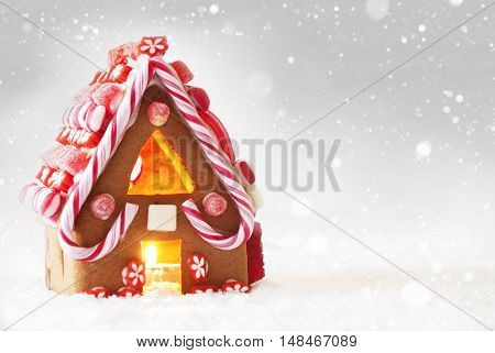 Gingerbread House In Snow As Christmas Decoration. Candlelight For Romantic Atmosphere. Copy Space For Advertisement. Silver Background With Snowflakes